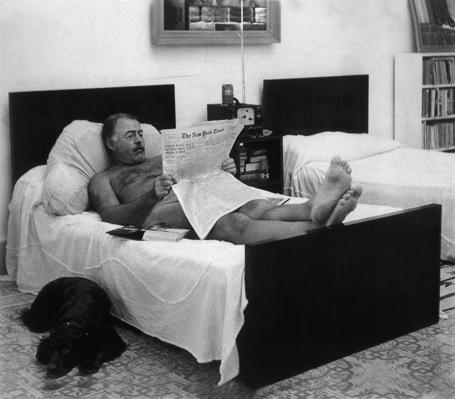 Ernest Hemingway , bem folgado, lendo o The New York Times, em foto deGeorge Leavens.