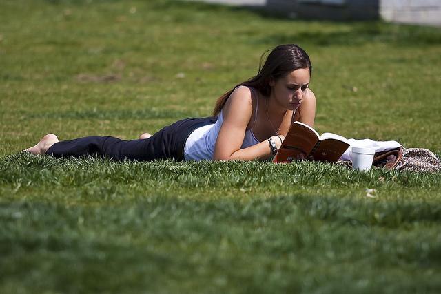 Mulher lendo na grama. Foto de Jeffrey Pott