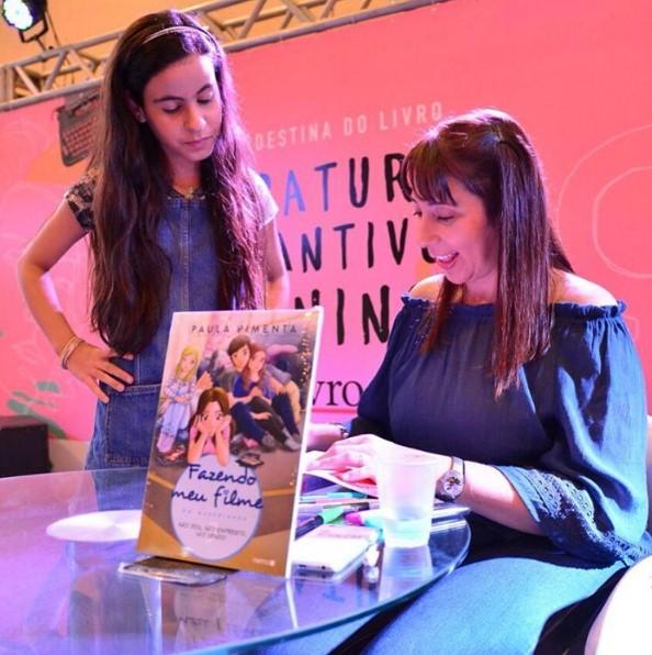 Clara pegando autógrafo de Paula Pimenta.